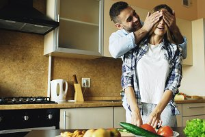 Young man covering girlfriends eyes with hands and surprising her in the kitchen at home