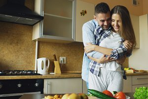 Happy young couple embracing and talking in the kitchen while cooking breakfast at home