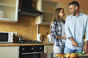 Happy young couple kissing embracing and chatting in the kitchen while cooking breakfast at home
