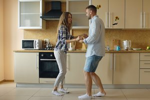 Attractive young funny couple have fun dancing while cooking in the kitchen at home