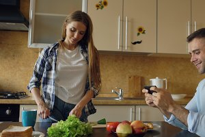 Attractive couple in the kitchen. Man playing video game on smartphone while his girlfriend cooking