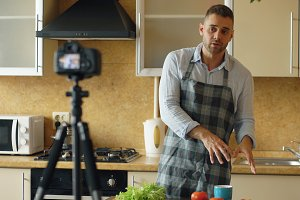 Young handsome man in apron shooting video food blog about cooking on dslr camera in kitchen