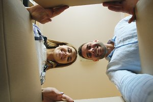 Young happy couple opening cardboard box after relocation and looking inside in new house