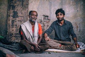 Two Men Sitting On Roadside