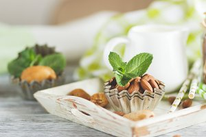 Honey in the wooden bowl, mint leaves, almonds and jar with milk on the wooden tray