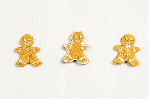 Gingerbread men friends on a white wooden table.