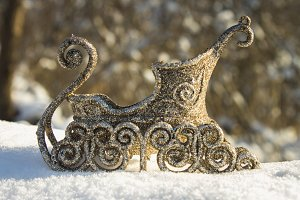 Golden sleigh in the snow. Christmas toys.