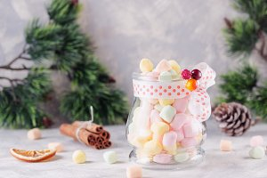 jar with marshmallows for Christmas and New Year on a wooden white table, selective focus