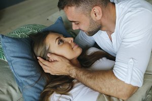 Young beautiful and loving couple wake up at the morning.