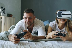 Young couple lying in bed play video games with controller and VR headset