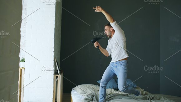 Young man singing to hair dryer and dancing rocknroll on bed in bedroom