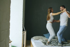 Young beautiful and loving couple dancing on bed in morning