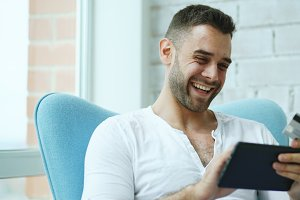 Young smiling man doing online shopping using digital tablet computer sitting at balcony at home