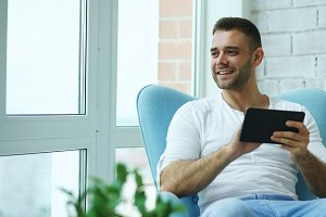 Attractive smiling man using digital tablet sitting in chair at balcony in loft modern apartment