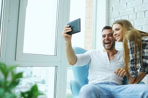 Young attractive couple having online video chat using tablet computer sitting at balcony in modern loft apartment