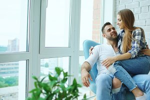 Beautiful young couple relax sitting on chair and enjoying view from balcony of new loft apartment