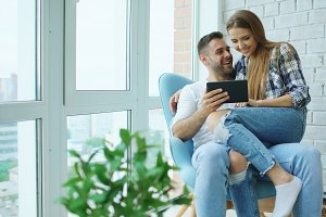 Young cheerful couple talking and using tablet computer on balcony in modern loft apartment
