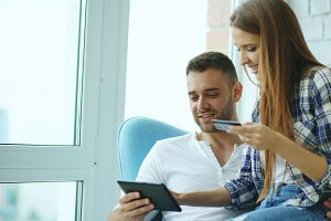Young cheerful couple using digital tablet computer for online shopping sit on balcony in modern loft apartment