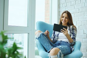 Young happy woman have online video chat using digital tablet computer sitting on balcony in modern loft apartment