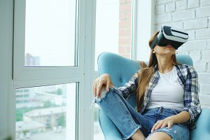 Young woman have VR experience using virtual reality headset sitting in chair on balcony