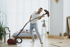 Young man having fun cleaning house with vacuum cleaner dancing