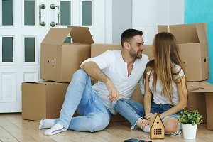 Happy couple sitting on floor in new house