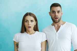 Portrait of young couple actively surprising and wondering looking into camera on blue background