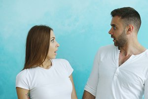 Portrait of young couple actively surprising and wondering looking each other