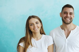 Portrait of young happy couple smiling and laughing into camera on blue background