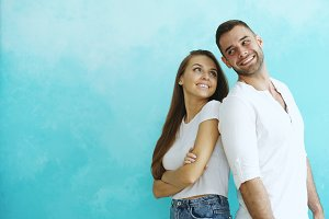 Young couple standing back to back flirting each other on blue background