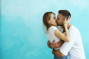 Young happy couple kissing on blue background