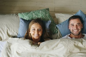 Top view of smiling couple having fun in bed hiding under blanket and looking into camera