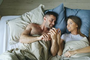 Top view of young couple lying in bed and talking each other smiling
