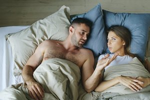 Top view of young couple lying in bed upset and argue each other