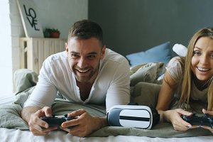 Young couple playing video copmuter games lying in bed at home