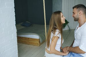 Happy loving couple sitting in swing in bedroom at home