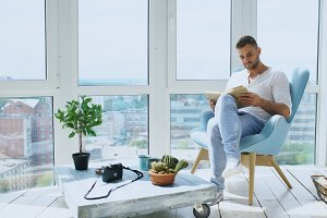 Young man read book sitting on balcony in modern apartment