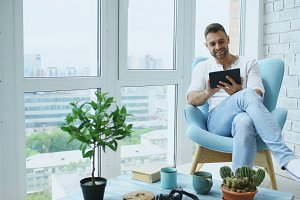 Attractive man using digital tablet sitting in chair at balcony in loft modern apartment