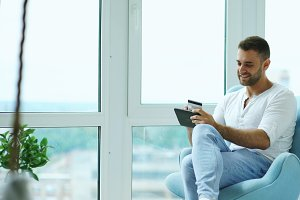 Young smiling man doing online shopping using digital tablet computer sitting at balcony in modern loft apartment