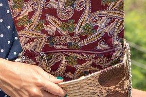 Woman hands with fashionable snake leather exotic handbag outside. Bali island.