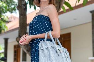 Closeup attractive beautiful woman with snakeskin python handbag posing outdoors. Bali island.