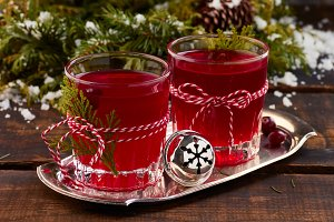 Two glases of cranberry fruit drink on old wooden table.