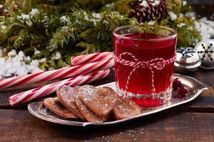 Glass of cranberry fruit drink and ginger cookies on metal plate over old wooden table.