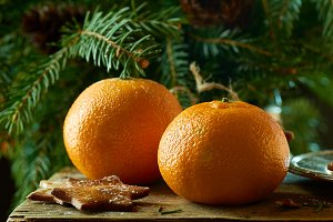 Tangerines and ginger cookies on spruce branches background