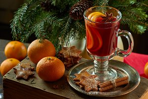 Mulled wine with cinnamon sticks, tangerine, ginger cookies and spruce branches