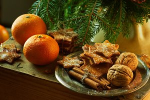 Tangerines and plate with ginger cookies, cinnamon sticks, walnuts on spruce branches background