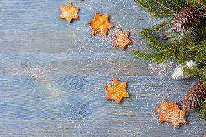 Star shaped ginger cookies and spruce branches with cones on blue wooden background text space.