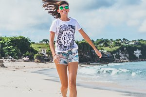 Sporty and healthy young woman in sunglasses running on the tropical beach. Bali island, Indonesia.