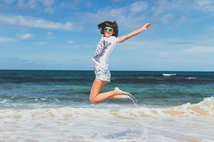 Happy free young sexy woman in sunglasses jumping on the beach of tropical island of Bali, Indonesia.