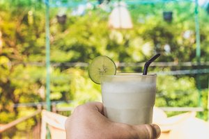 A glass with fresh organic lime juice in man hand on a beautiful nature background. Bali island, Indonesia.